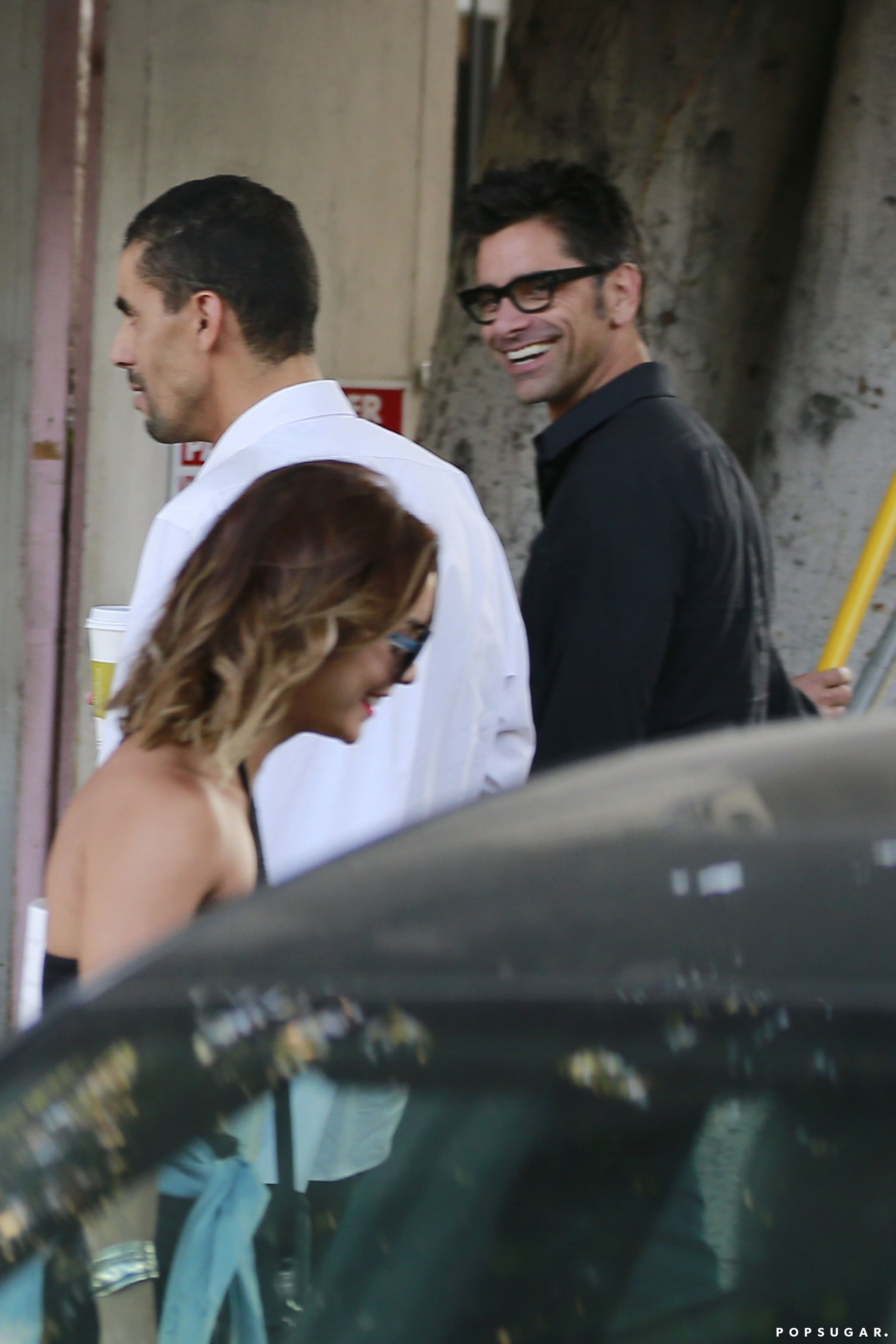 Vanessa Hudgens and John Stamos smiled when they spotted each other at the salon valet in LA on Friday.