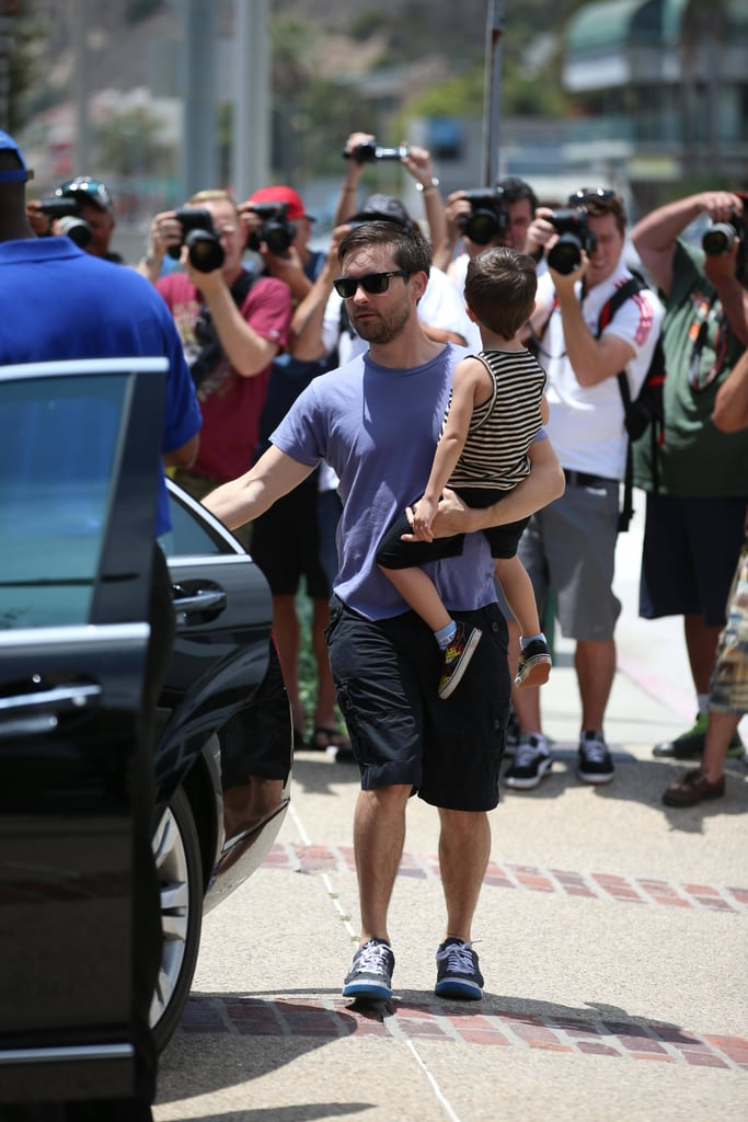 Tobey Maguire carried his son, Otis, to a Memorial Day beach party in Malibu, CA.