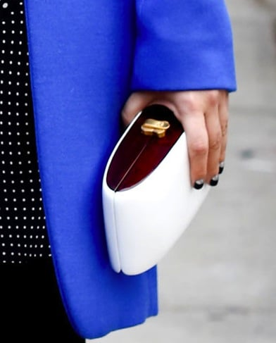 The wood detailing gives this structured white clutch a modern pop.