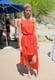 This chic look comprised a multicolored turban, a bright orange high-low maxi dress, and metallic sandals. Source: Chi Diem Chau