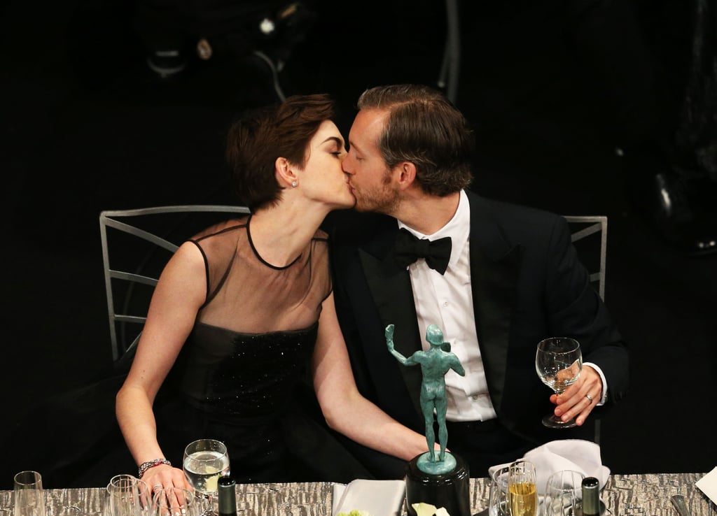 Anne Hathaway kissed husband Adam Shulman after picking up her statue for best supporting actress at the SAG Awards. See all the celebrity fun inside the SAGs.
