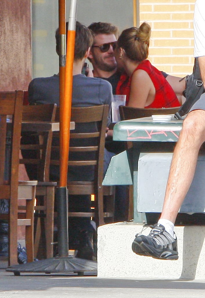 Miley Cyrus snuggled up to Liam Hemsworth while dining in LA in January 2012.