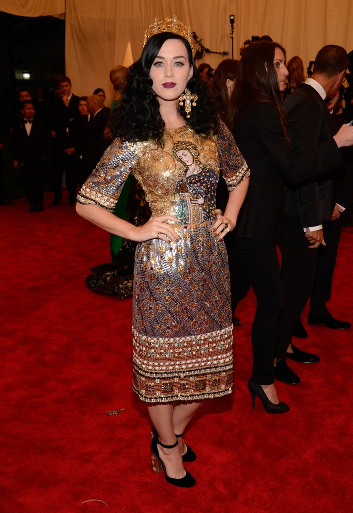 Posing in an opulent Dolce & Gabbana sheath accessorized with raven-hued locks, a guilded crown, and statement crucifix earrings, Ms. Perry's 2013 Met Gala look was all about dark decadence.