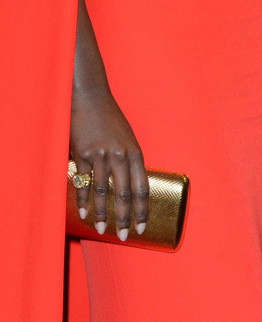 Lupita Nyong'o's gold Monica Rich Kosann clutch and Fred Leighton cocktail ring were just the right accents against her red gown.