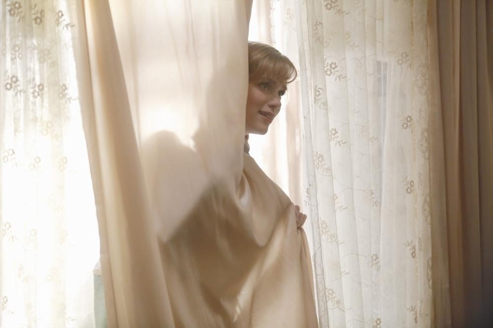 Anna hides in the curtain.