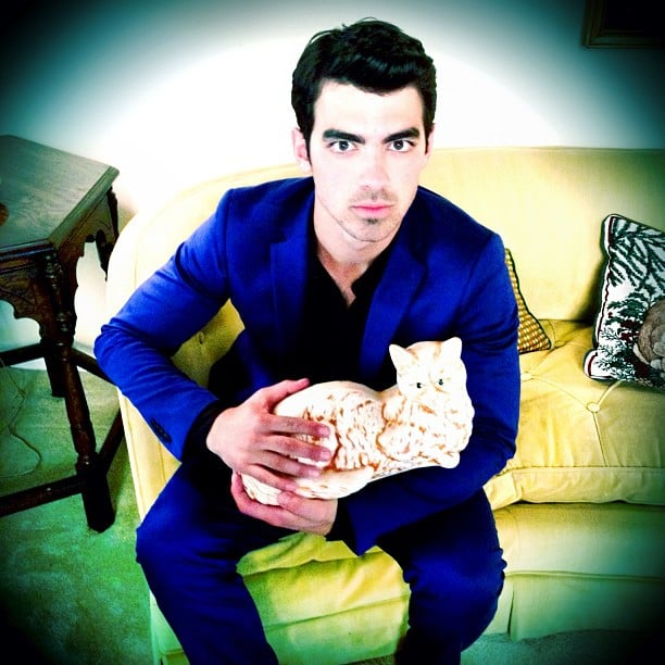 Joe Jonas posed in a blue suit with a ceramic cat. Source: Instagram user adamjosephj