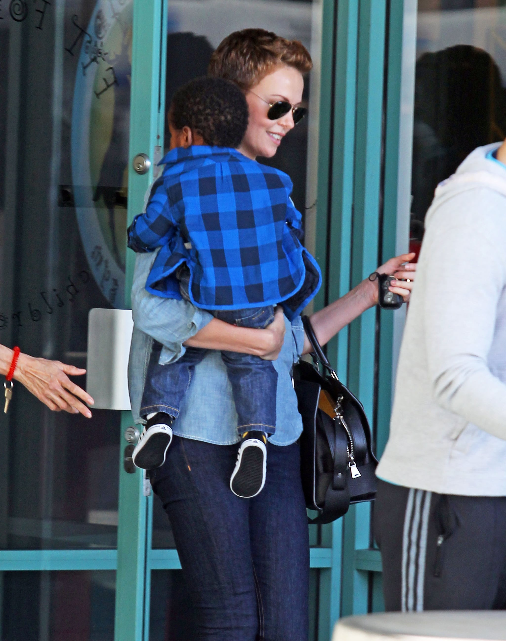 Charlize Theron smiled on her way out of the gym with son Jackson in her arms.