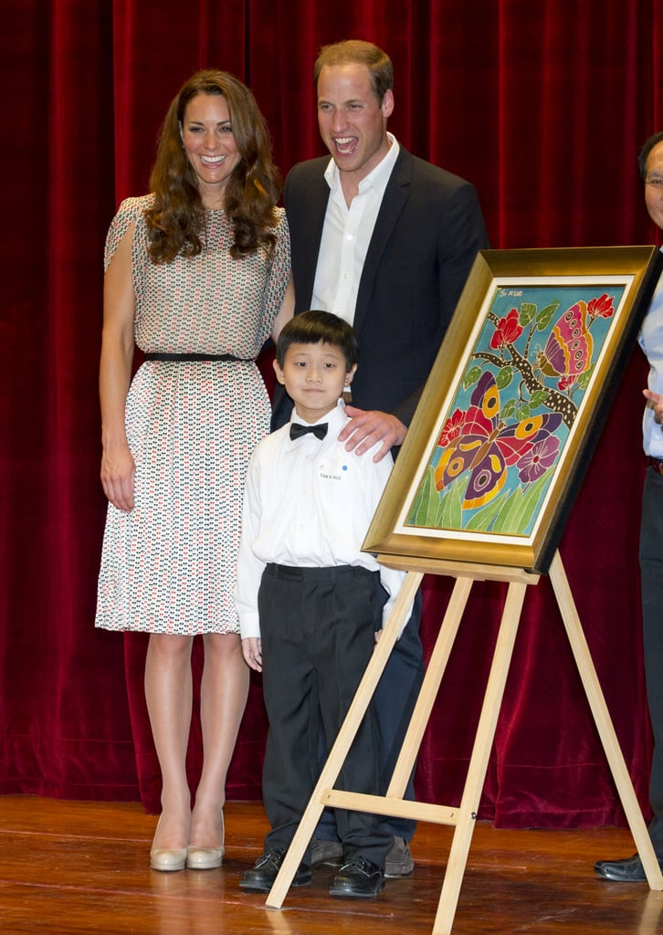 The couple posed proudly with a young artist during their visit to the Rainbow Center in Singapore. The stop was part of their Diamond Jubilee tour in September 2012.