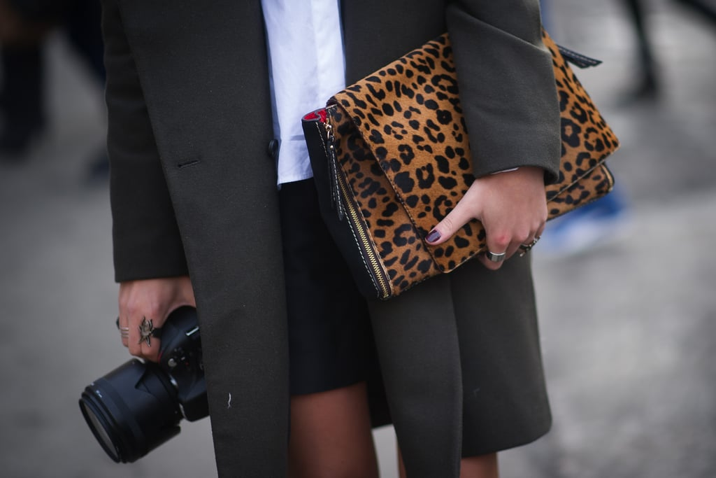 Double-fisting two Fashion Week essentials: a camera and a chic clutch.