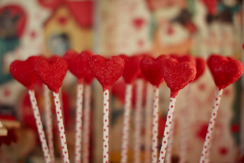 Candy-heart pops with a red polka-dot stem served as both decor and a sweet treat.  Source: Jenny Cookies