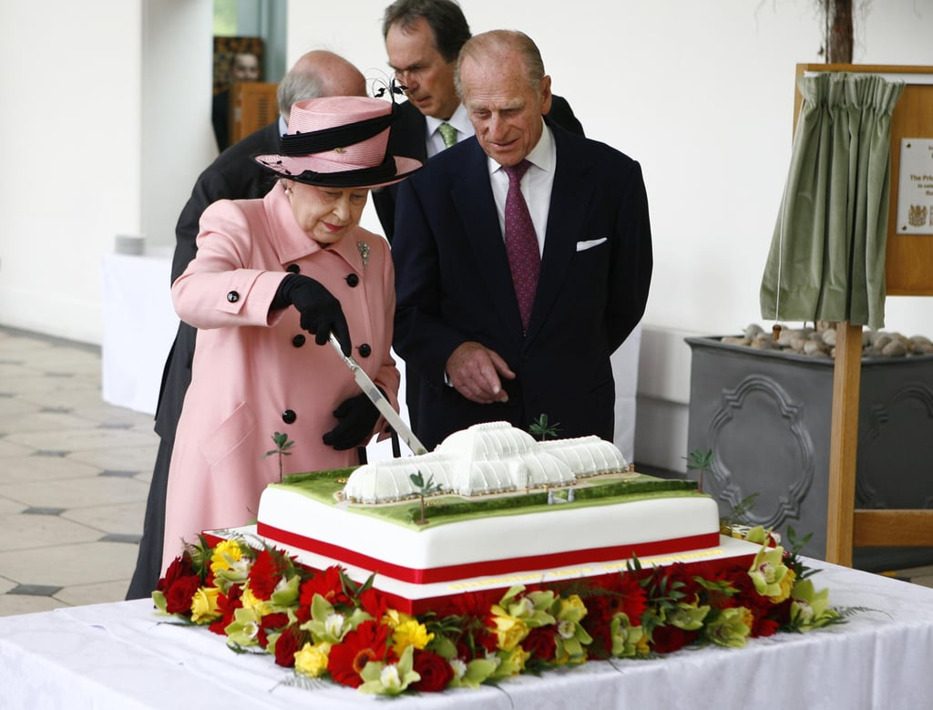 Queen Elizabeth II cut a cake during a visit to The Royal Botanic Gardens in Kew on May 5, 2009 in London, with Prince Philip looking on.