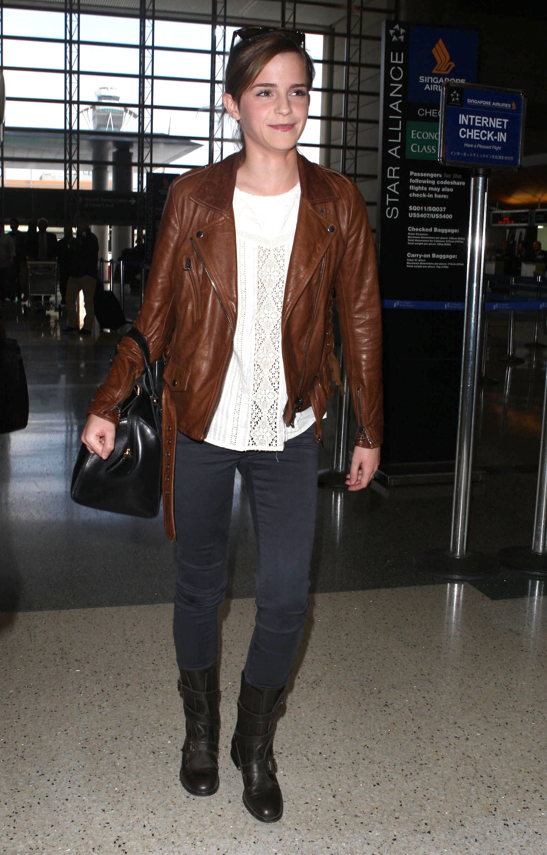 Emma Watson added edgy polish to her airport ensemble with the help of a brown motorcycle jacket and AG velvet jeans.