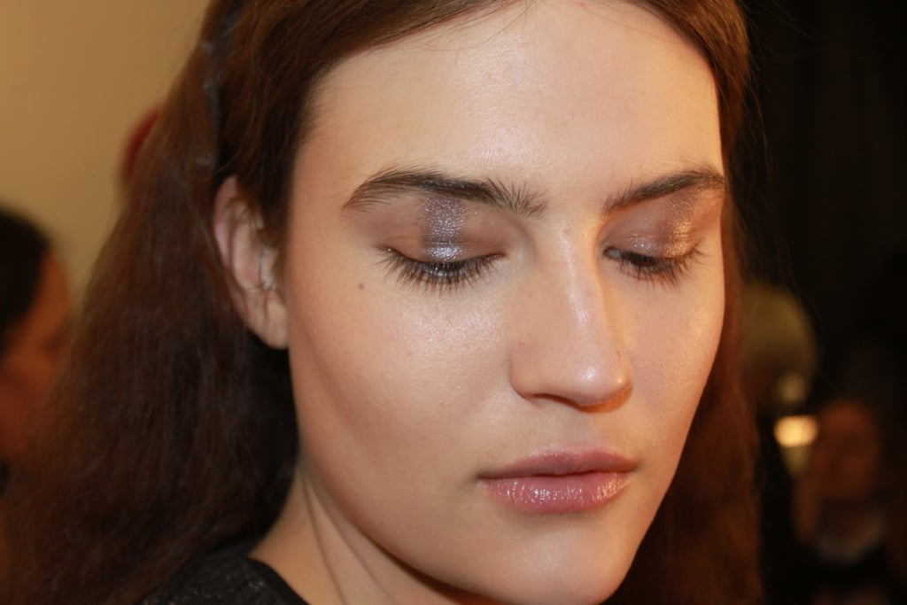 """""""I'm creating a ray of light on the eye with a metallic strip in a cold nude color right in the middle,"""" makeup artist Tom Pecheux explained. To get a rectangular shadow shape on the eye, he used three different shimmer shadows blended together: Estée Lauder Color Instant Intense Eye Shadow Trios in Smoked Chrome, Steel Lilacs, and Sterling Plums. """"Makeup today is very minimal. The inspiration is based on a comfortable, homey, casual indoor place,"""" he said."""