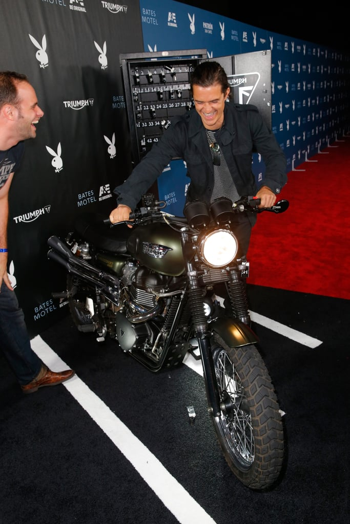 Orlando Bloom lit up while checking out a motorcycle on the red carpet at Playboy and A&E's Bates Motel event on Friday.