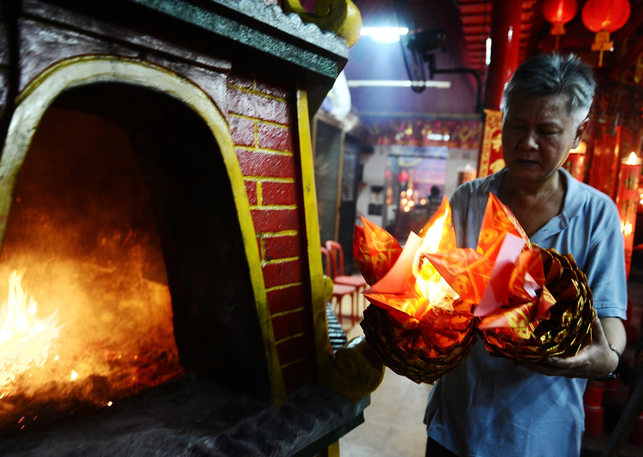 A man burned papers while praying at Hong San Ko Tee Temple in Surabaya, Indonesia.