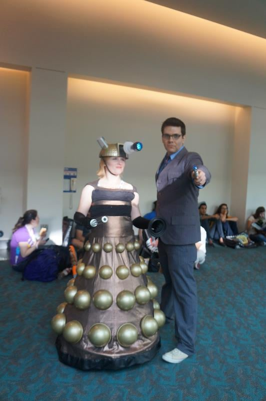 A regal Dalek and Doctor make their way through the convention hall.