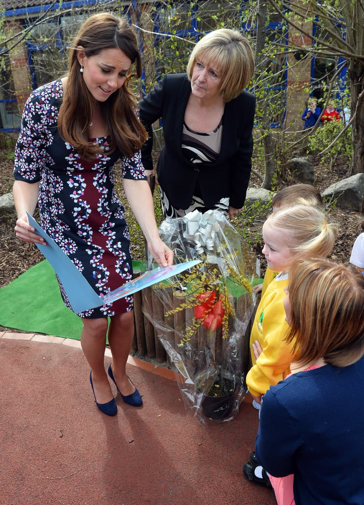 Kate received a giant book from schoolchildren at the Willows Primary School in Manchester, England. She showed off her growing baby bump in a printed dress during the April trip.