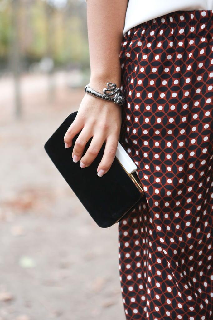 An artful balancing act — a minimalist clutch met printed pants.