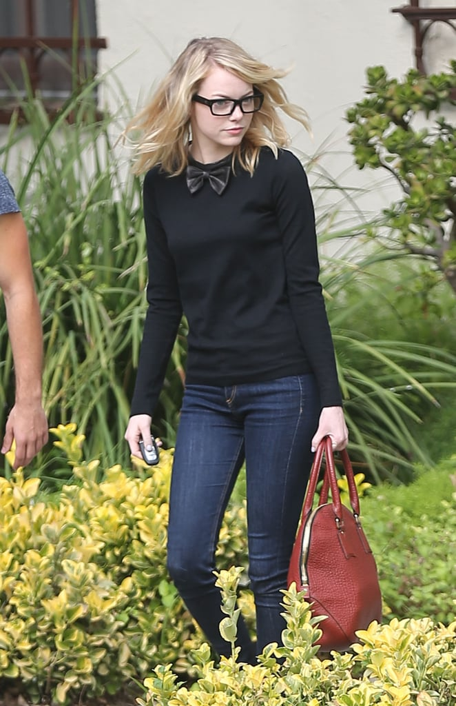 Emma Stone wore a black bow-tie sweater and black frames.