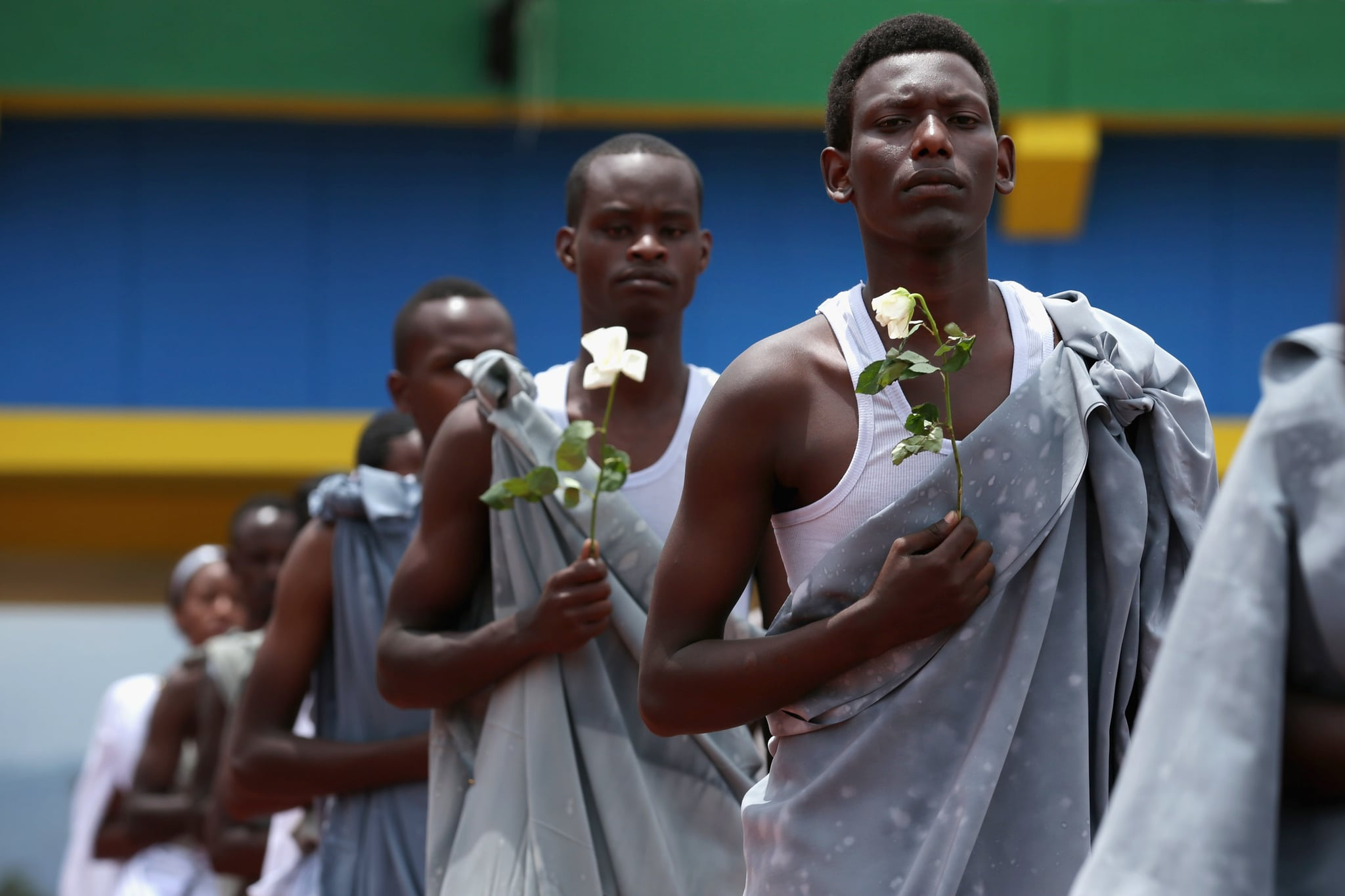 Performers carried white flowers as they entered Amahoro Stadium, where tens of thousands of Rwandans gathered to remember the 100-day massacre.