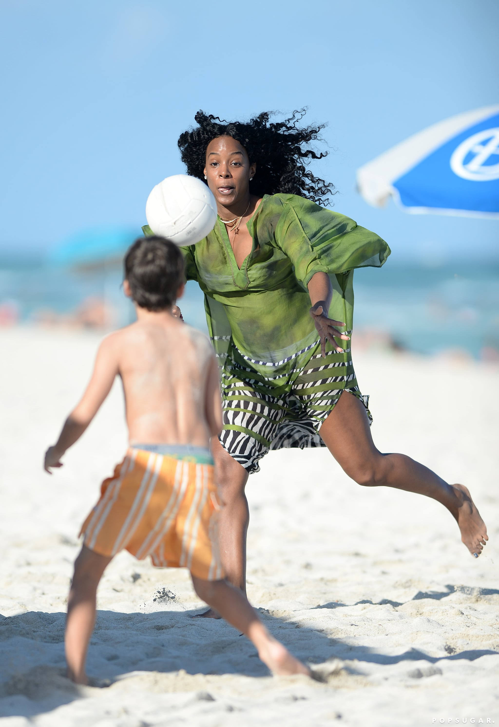 Kelly played soccer with kids on the beach.