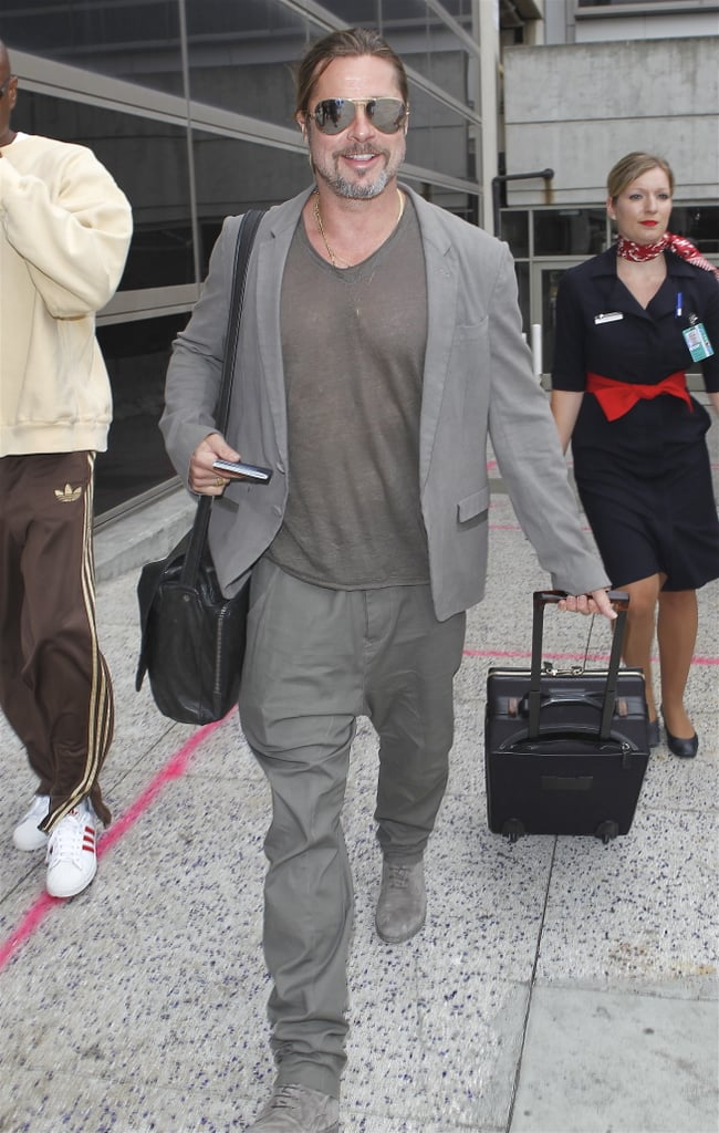 Brad Pitt flashed a smile as he touched down at LAX following a trip to France.