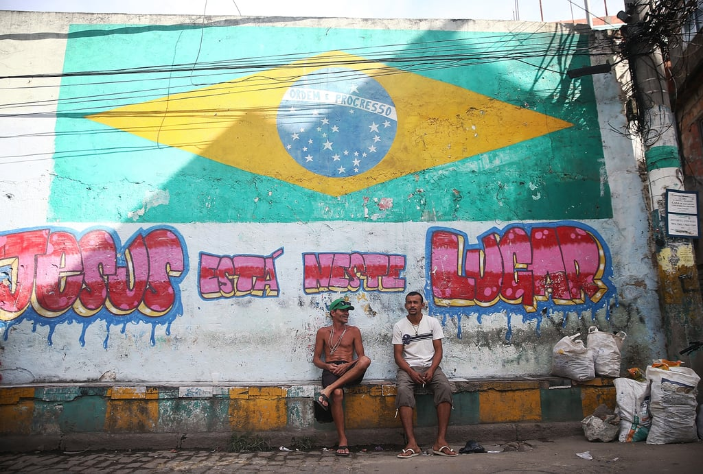 People sat beneath a painted flag in Rio de Janeiro.