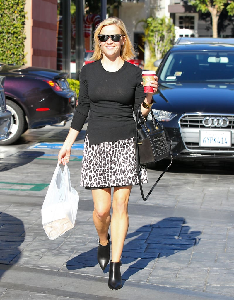 Witherspoon tempered her leopard skirt and patent leather booties with a simple sweater and perforated Reed Krakoff bag.