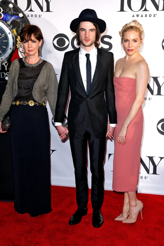 Sienna Miller walked the red carpet with beau Tom Sturridge and Phoebe Nicholls in a soft coral-hued strapless Burberry dress and nude pumps.
