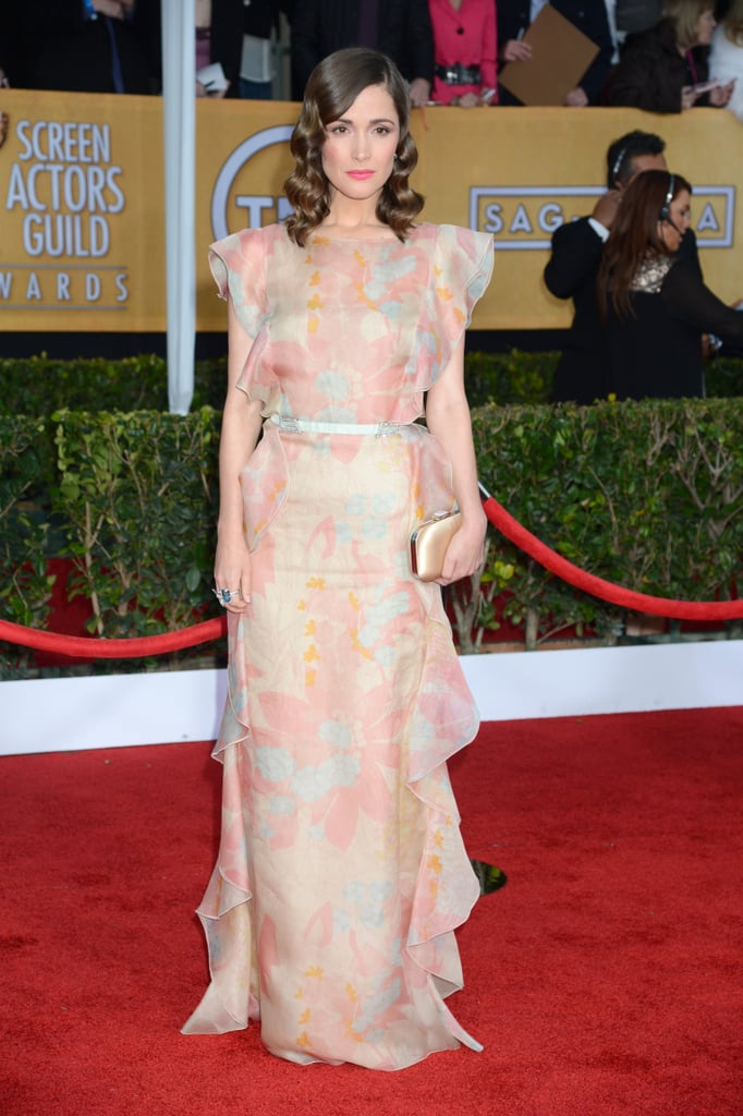 Rose Byrne blossomed in a floral ruffle-detail Valentino gown, soft curls, a gold satin Jimmy Choo clutch and punchy pink lip.