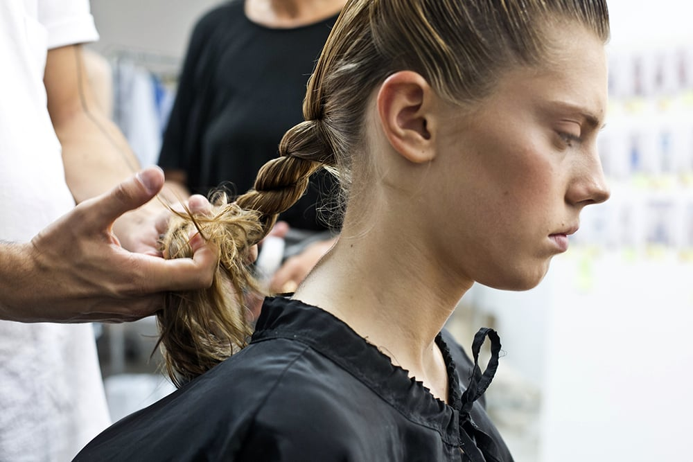 Next, Odile twists the hair within the ponytail.