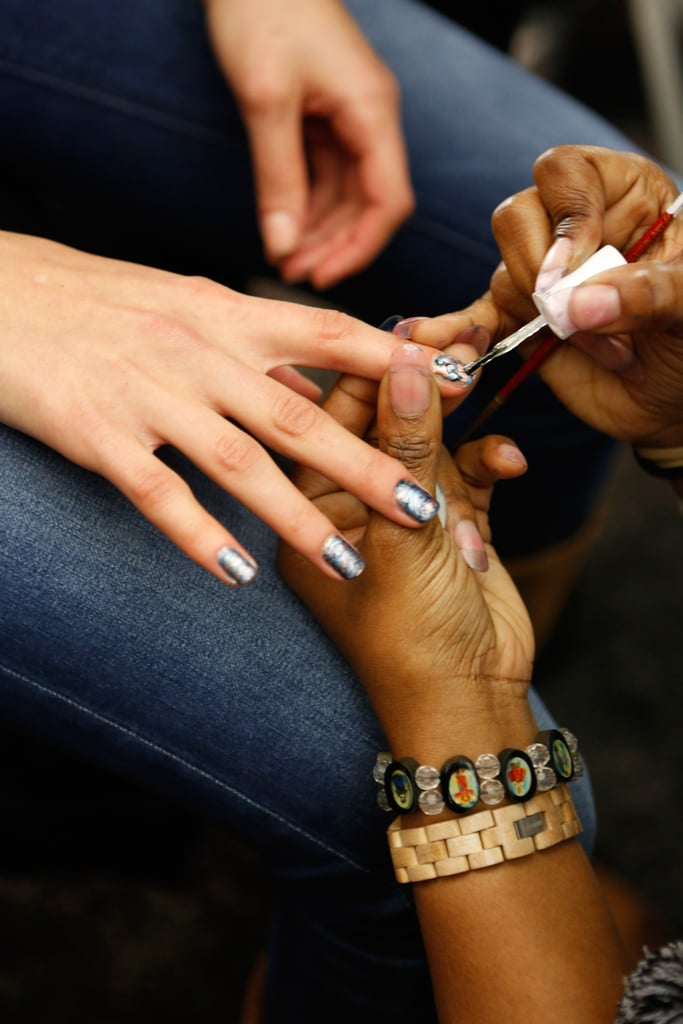 """To create the look, Saunders and her team painted each nail by hand using five different Essie shades with metallic or cream finishes: Aruba Blue, Go Overboard, Blue Rhapsody, Penny Talk, and As Gold As It Gets. Starting with the darkest shade, dabs of polish were placed on the nail, followed by a couple drops of the other colors, from darkest to lightest. Superfine-tipped brushes were then used to swirl the paint around. """"You only want to make three to four strokes, or else the paint will start to blend,"""" Saunders explained."""