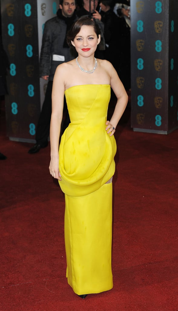 Marion Cotillard battled the grey skies in a vibrant yellow Christian Dior Haute Couture gown at the BAFTA Awards in London. The actress accessorised with a swept updo, red lipstick, and a dazzling diamond necklace by Chopard.
