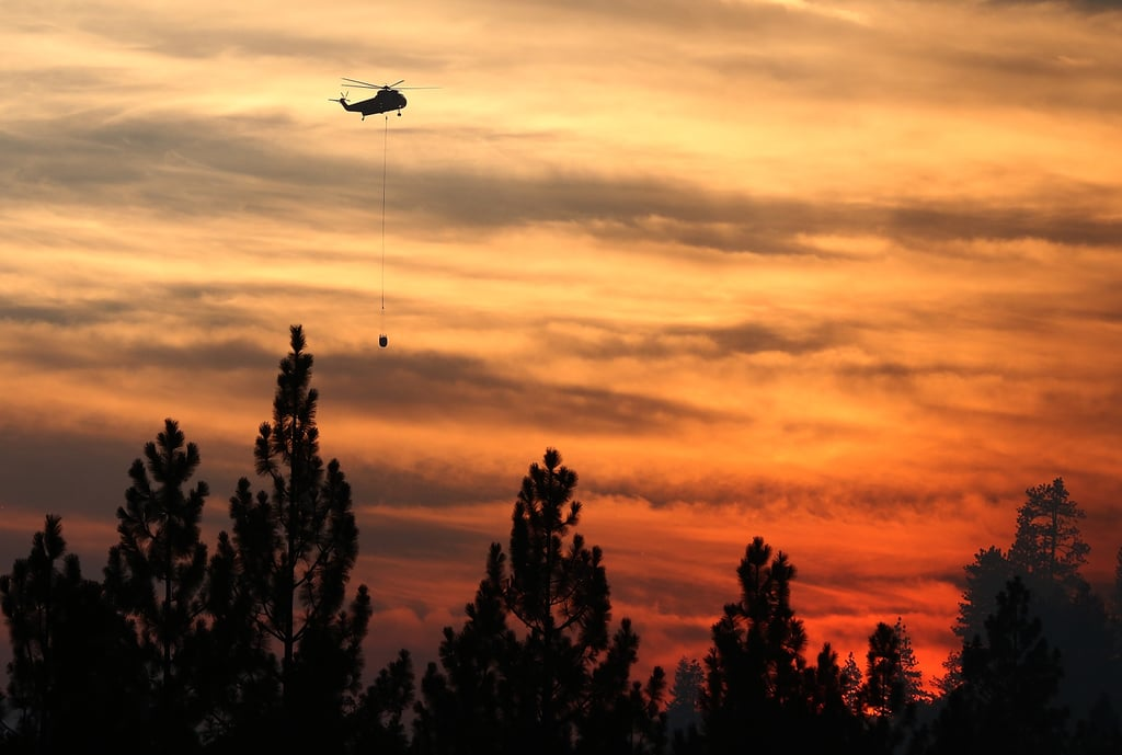 A helicopter dropped water on the fire near Groveland, CA.