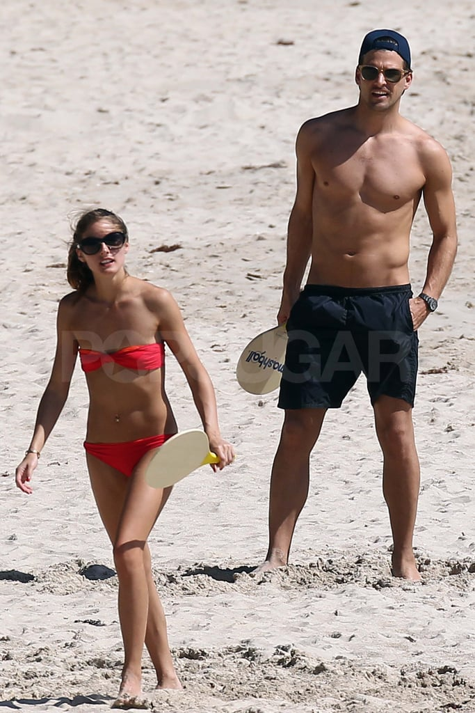 Olivia Palermo in a bikini playing paddleball with shirtless Johannes Huebl.