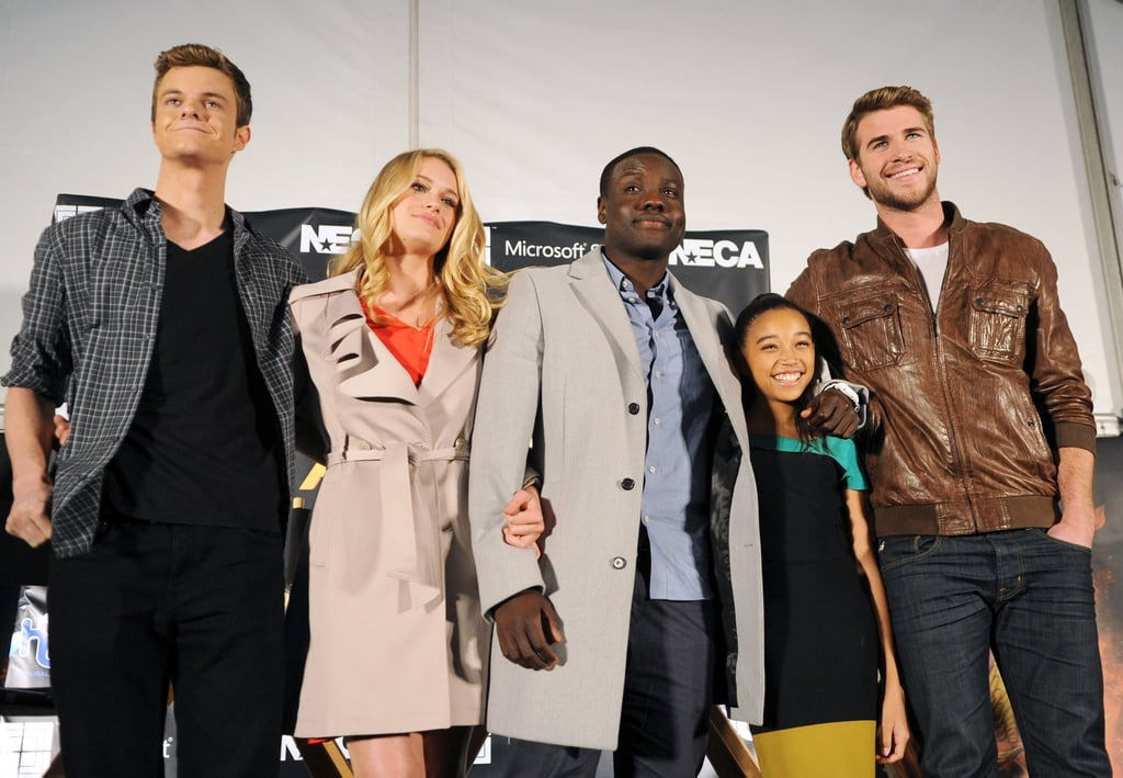 Liam Hemsworth put his arm around his youngest costar, Amandla Stenberg, as they posed with Dayo Okeniyi, Levin Rambin, and Jack Quaid.