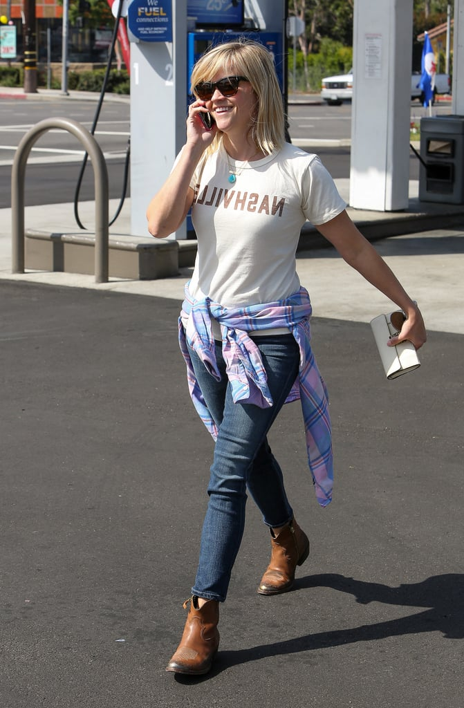 Witherspoon flaunted her Southern roots with a Nashville tee, Gold Sign denim, and rustic ankle boots — all wrapped up with a plaid Rails shirt.