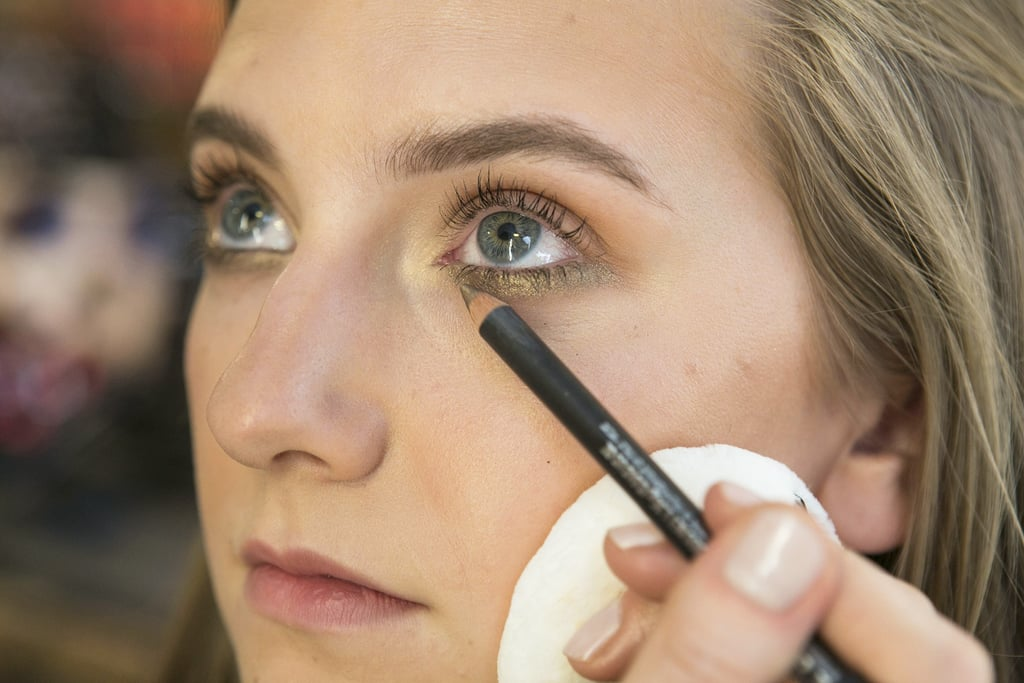 """Now that the skin is warmed up and bronzer has been applied, Betelli likes to use a bronzed makeup palette to create a sultry Summer look. She started off with Eye Kohl in Powersurge ($16), a bronze-brown with golden shimmer, inside the water line and under the eyes for a soft smoky look. """"My trick is to make the line extend out to where your lashes end,"""" she says."""