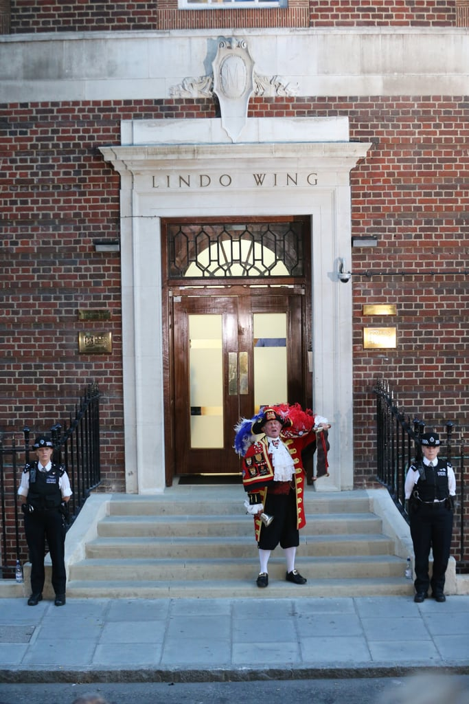 """A """"town crier"""" stood on the steps outside St. Mary's Hospital in London to share the news."""