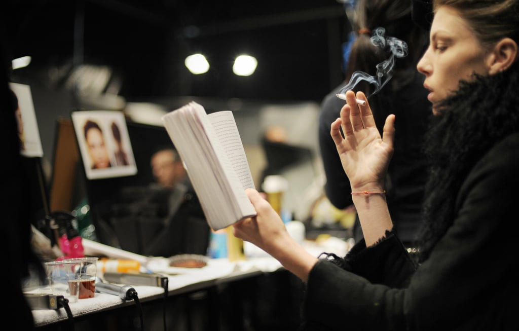 A model read while smoking a cigarette backstage during Milan Fashion Week in 2008.