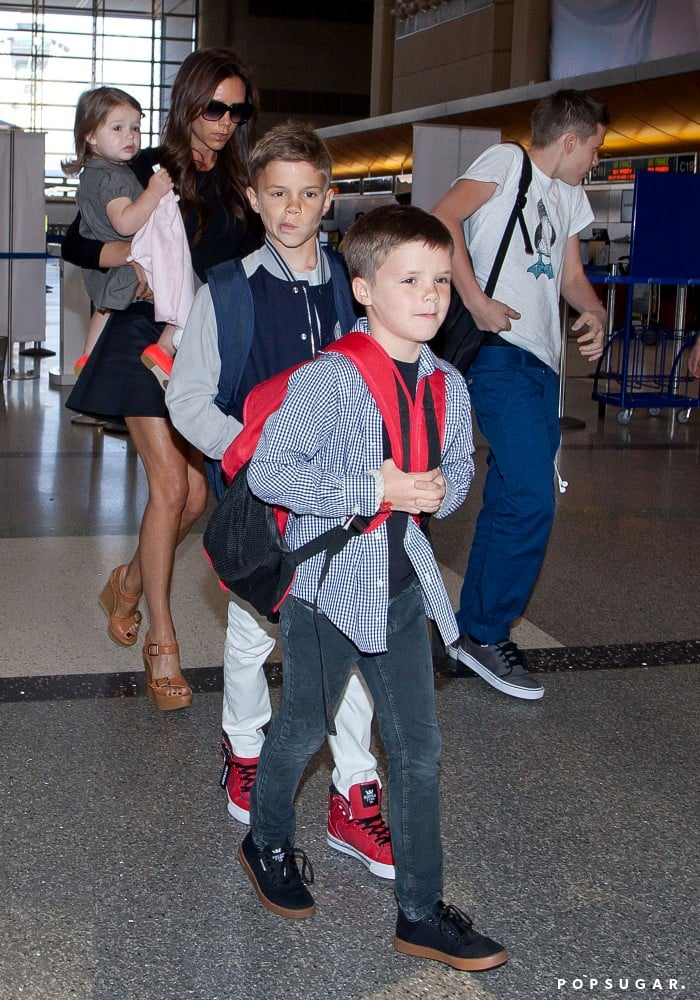 Victoria Beckham showed off her legs while traveling from LAX with her kids.
