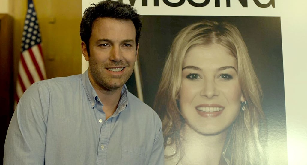 """Nick (Ben Affleck) makes a mistake when he smiles smarmily in front of his wife's """"Missing"""" poster."""