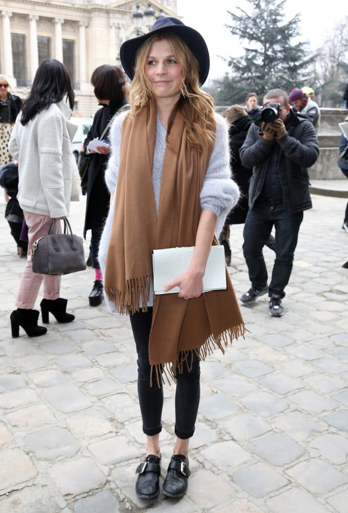 Clémence Poésy layered up in a mohair sweater, a camel scarf, and a wide-brim hat outside Acne.
