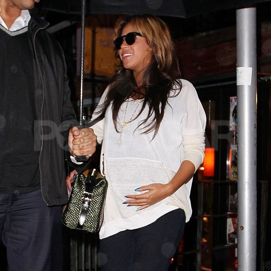 Beyoncé Knowles held onto her belly with her bright blue nails.