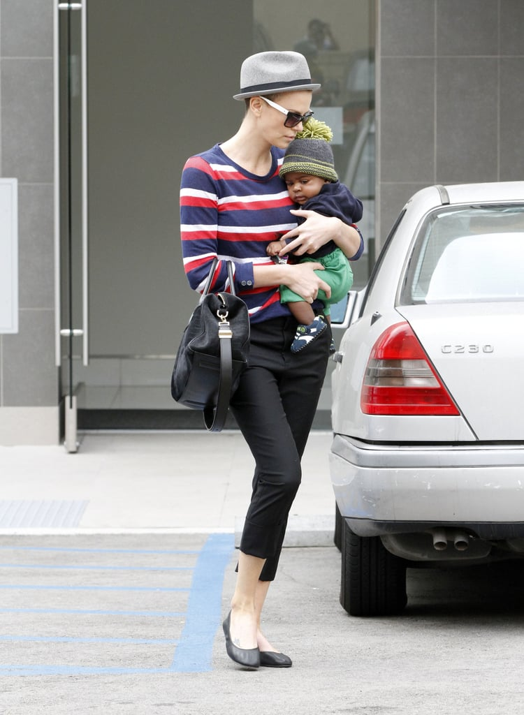 Charlize Theron looked cute in black cut-offs with baby Jackson in her arms.