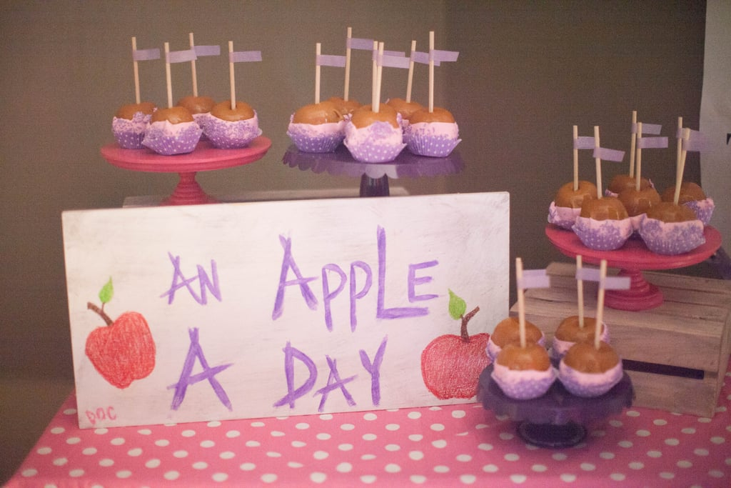"""""""With all the candy from the pharmacy and sweets on the dessert table, we thought we'd offer our guests some fruit,"""" Jenny said. """"So we did an 'Apple a Day' table filled with purple and pink chocolate-dipped caramel apples. Source: Jenny Cookies"""