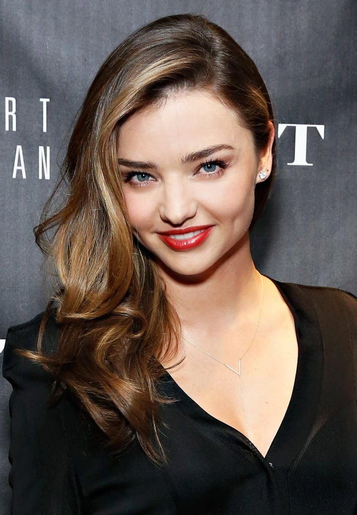 Sticking with her signature sideswept waves, Miranda Kerr completed the look with glossy red lips.