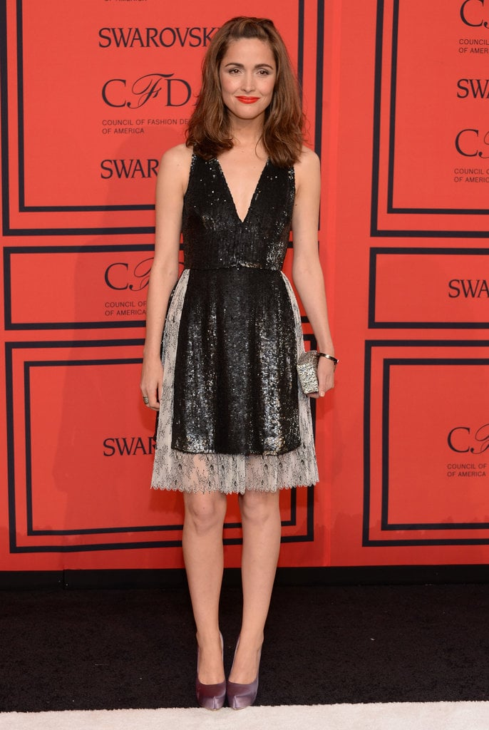 Rose Byrne balanced dainty with sassy in a black sequined v-neck dress and purple satin pumps.