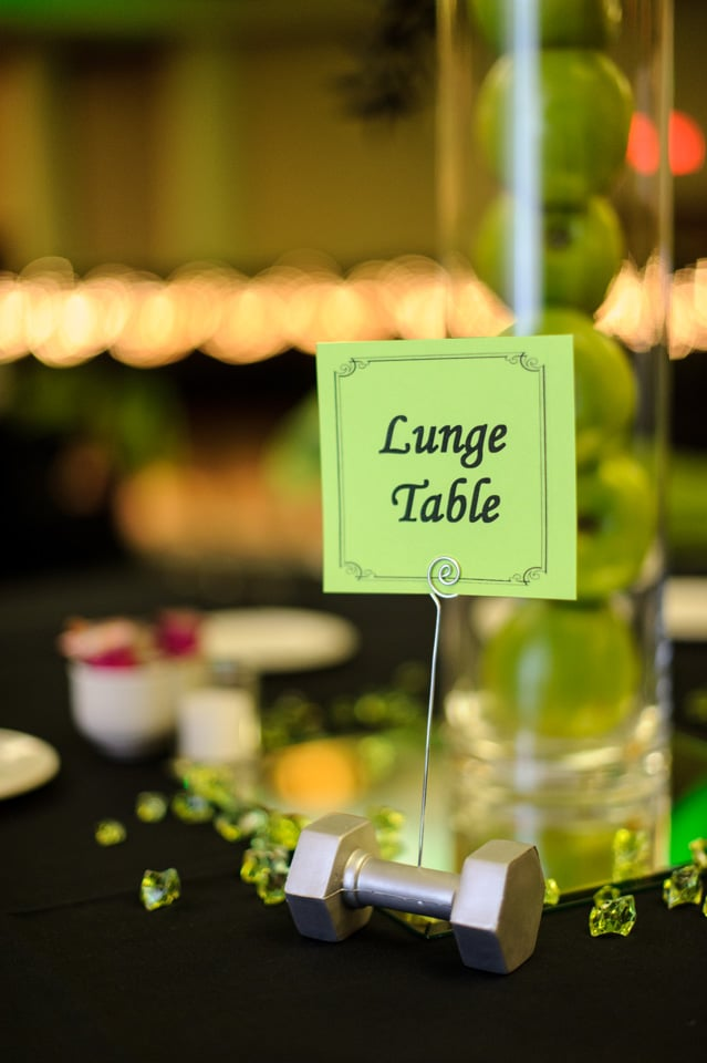 Small details made a big impression on wedding guests. Tables were decorated with flowers, fresh apples, and plenty of dumbbells to go around! To stay in line with the fit theme, each table was named after a different exercise.