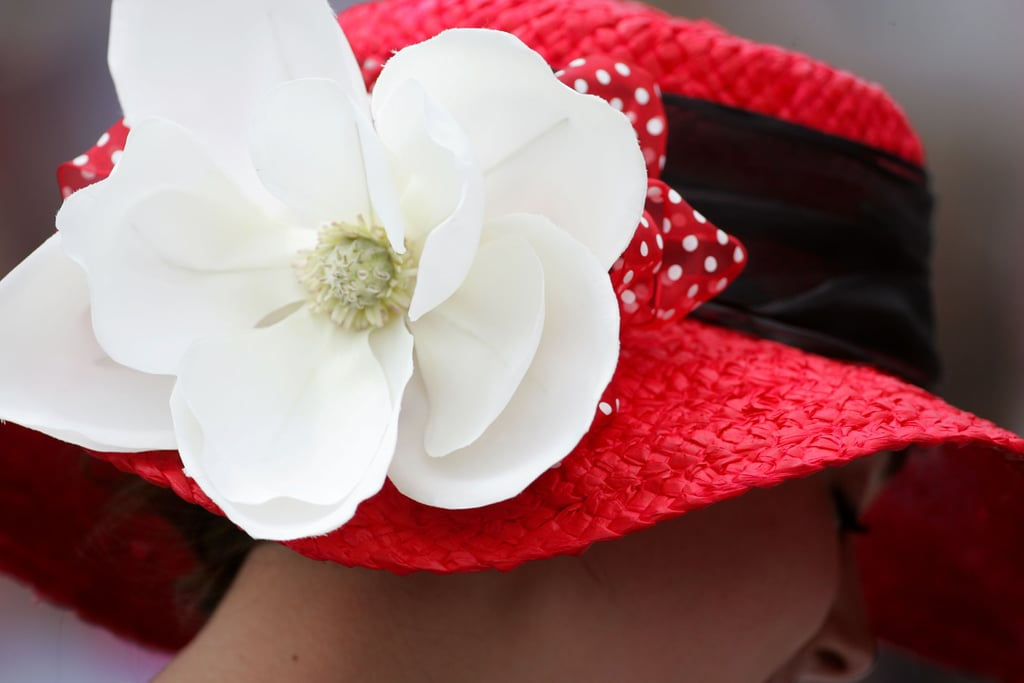 A woman wore a bright red hat with a big white flower to the 2011 race.
